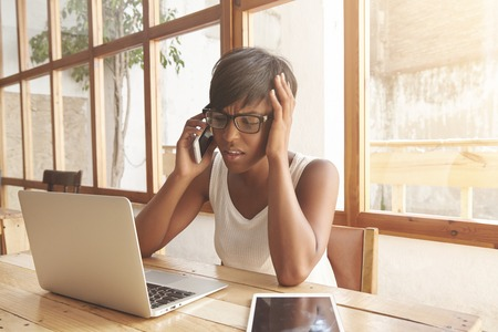olive skin: Attractive woman with olive skin and dark short hair solving business problems in coworking place. Smart young girl in glasses and white sleeveless has all the gadgets for successful work nearby.