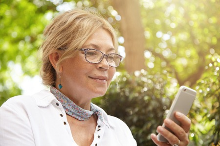 People, technology and communication concept. Attractive senior female writer in spectacles using generic smart phone for publishing new post on social networks, spending her free time on blogging LANG_EVOIMAGES