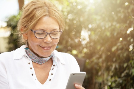 Headshot of good-looking modern blond mature woman wearing glasses, messaging her grandson via social networks, using her generic cell phone, smiling while reading message or looking at photo LANG_EVOIMAGES