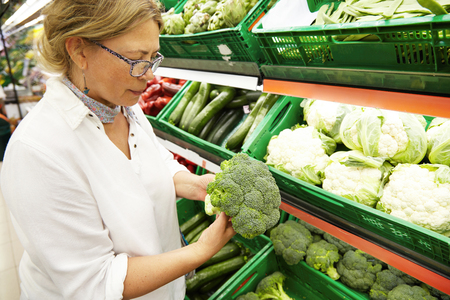Close-up profile portrait of good-looking middle-aged Caucasian woman vegetarian in casual clothes picking-up and choosing the freshest vegetables and broccoli at grocery store. People and shopping