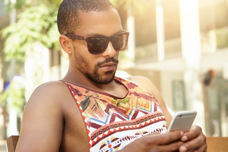 people: Famous trendy African blogger in shades hiding from summer heat in park using smart phone for sharing his new post via social networks, looking serious and concentrated. Black man texting outdoors LANG_EVOIMAGES