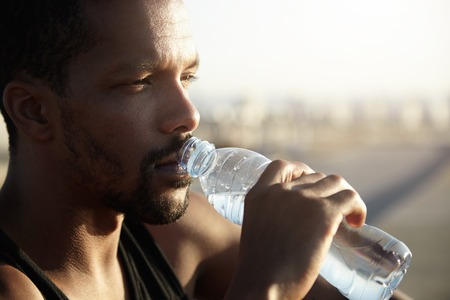 dark skinned: Attractive young dark skinned sportsman with short beard drinking water from bottle looking far away with thoughtful face expression, dressed in black sleeveless shirt, relaxing after morning run