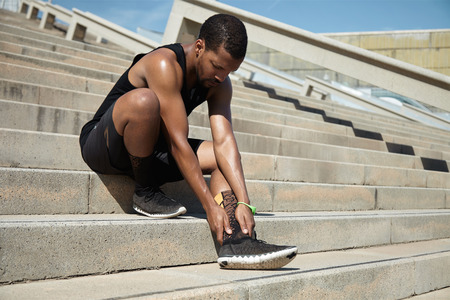 Muscular dark-skinned male athlete in black sportswear holding his injured leg with both hands, massaging his ankle, suffering from sprain during physical training outdoors, preparing for marathon Stock Photo