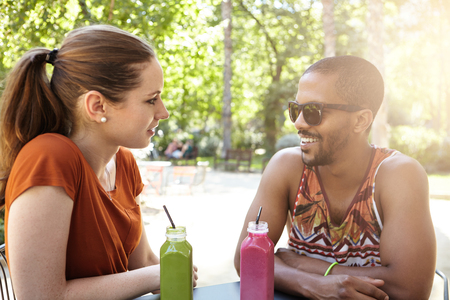 mates: Interracial friendship. College mates in park sitting at cafe with healthy juice. Caucasian woman and dark skinned man nice chatting about good old days, next academic year, dream job and career