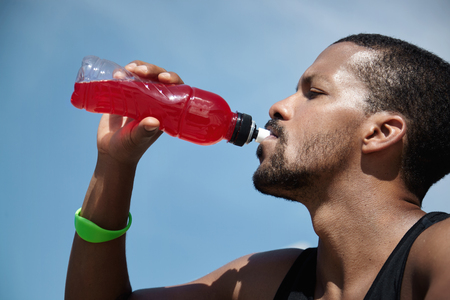 Headshot of exhausted African American athletic runner with sweaty skin wearing sleeveless black shirt, quenching his thirst with red juice or shake, relaxing after hard workout training outdoors Standard-Bild