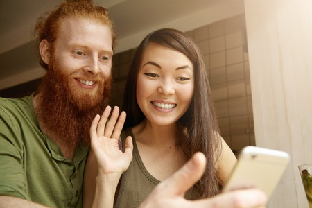 congratulating: Young cute couple recording video for congratulating their friend on his birthday. Pretty student girl saying hello while taking selfie together with her redhead boyfriend using electronic device