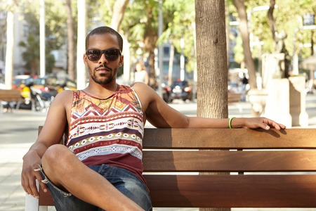 People and lifestyle concept. Black bearded guy in colorful tank top and denim shorts sitting on bench under a tree in city park on sunny day with serious look, waiting for his friends to come Stock Photo