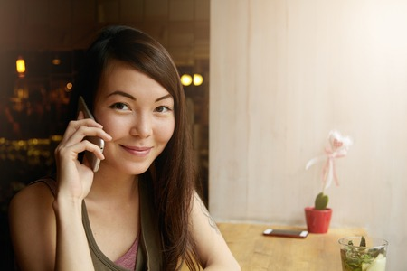 phone calls: People and communication concept. Headshot of beautiful young female making phone calls, talking to her friends using gadget, inviting them to her place at weekends while sitting at cafe table Stock Photo