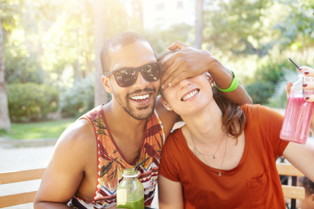 closing time: Best friends sitting at cafe in city park drinking fresh juice. Caucasian woman and dark-skinned man chatting, laughing, having good time together, man closing his girlfriends eyes with hand Stock Photo
