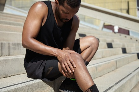 Handsome muscular male jogger wearing black training outfit touching his knee in pain with clasped hands, having sprain or rupture in his muscles after exercising outdoors. Sports injury concept