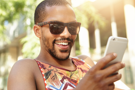 Outdoor picture of young charismatic student in sunglasses using smart phone, African man smiling while surfing social networks, liking pictures and leaving comments via his web-enabled mobile phone