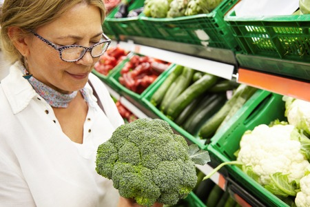 produce departments: Cropped shot of attractive elderly or middle-aged blond woman holding huge fresh green broccoli standing in front of shopping window with various vegetables, examining it carefully before buying