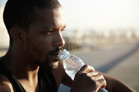Healthy lifestyle concept. Profile portrait of black man with athletic body sitting on pavement in morning sun after training exercises in open air, holding bottle, drinking water, looking far away