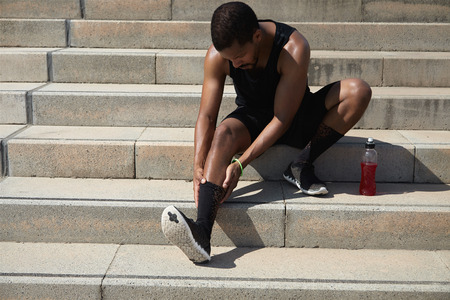 Dark-skinned athlete with muscular body wearing black outfit holding his injured leg with both hands, massaging his ankle, suffering from sprain after exercising outdoors, preparing for marathon Standard-Bild