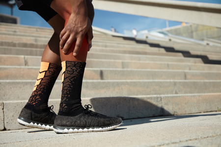 African jogger wearing black running shoes having strain or rupture in his calf, massaging it to soothe pain in muscle after intense jogging workout, standing against concrete stairs background Stock Photo