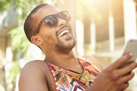 laughing out loud: Human emotions and feelings. Cute charismatic dark-skinned man holding smart phone, laughing out loud after receiving hilarious picture from best friend, against background of summer city landscape Stock Photo