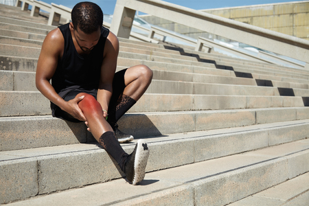 soothe: Attractive dark-skinned male runner wearing black outfit sitting on stairs outdoors, massaging his aching knee of red color, looking at sore skin with painful expression, trying to soothe pain
