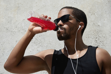 quenching: Headshot of exhausted dark-skinned runner in shades and earphones wearing black sleeveless shirt, quenching his thirst with red juice or shake, relaxing after intense physical activity outdoors