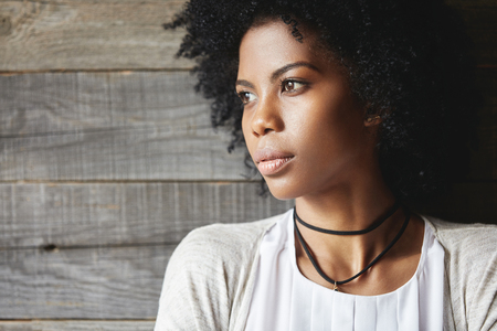 Highly-detailed profile portrait of beautiful dark-skinned young student girl with healthy skin and Afro haircut, wearing trendy clothes and choker, looking away with dreamy and pensive expression