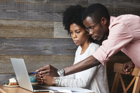 People and education concept. Young African teacher in glasses explaining new material on economics to his beautiful female student, pointing at laptop screen with pen while having lesson at cafe