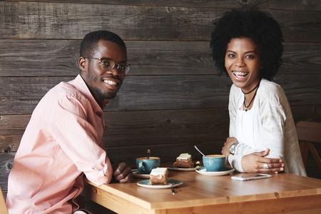 dark skinned: Indoor portrait of happy young African American students sitting at cafeteria having desserts and coffee looking with sincere smile. Black handsome man talking to his beautiful female college mate