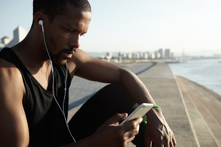 sleeveless top: Handsome dark-skinned jogger wearing black sleeveless top listening to music with headphones, browsing Internet using his smart phone while waiting for his friend to join him in morning run on beach