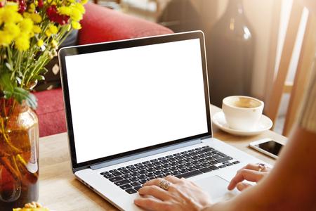 選択と集中。カプチーノを飲んで、自宅のテーブルに座ってコンピューター ラップトップを使用する友人とおしゃべりしながらキーボードで入力し