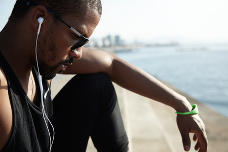 Sideways portrait of stylish sad African American boy looking down in black sunglasses and clothes. Young man is plunged into music and focused on his life problems, sitting alone near the water.