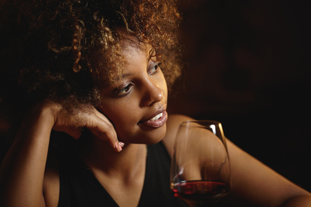 lounge bar: Fashionable African young lady with curlly hair at lounge bar, chilling, sitting at table with glass of red wine, resting her head on hand, looking thoughtful, dreaming and smiling mysteriously