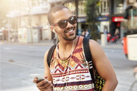 People, technology and communication. Charismatic young African traveler having walk on city street, talking to his friends on mobile phone using handsfree, laughing at jokes, looking happy and glad Stock Photo