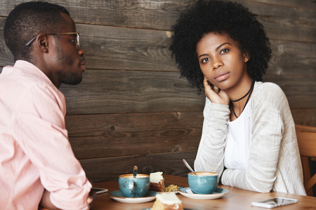 Two young black smart managers discussing very important question sitting at coffee shop, searching for new brilliant idea for developing strategy of successful business, woman having thoughtful look Imagens