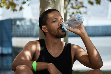 quenching: Fitness and healthy lifestyle concept. Portrait of muscular build jogger in sleeveless shirt holding plastic bottle of water, quenching his thirst, sitting under tree, resting after physical workout Stock Photo