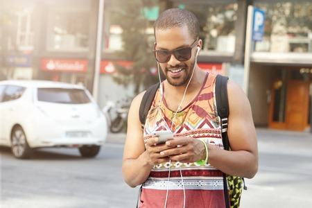 coming home: Portrait of attractive African athlete in sunglasses coming home after workout at fitness club, messaging via social networks and using earphones for listening to music. Healthy lifestyle concept