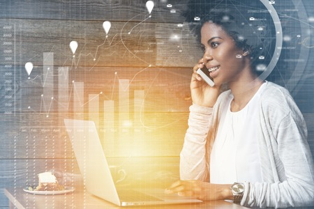distant work: Visual effects. Attractive dark-skinned female marketing expert using laptop for distant work at cafe, talking on mobile phone to her boss, discussing financial questions with smile on her face Stock Photo
