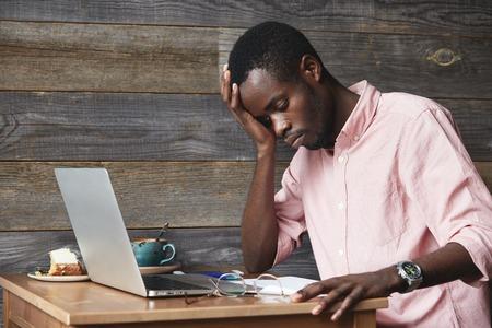Übermüdung Konzept. Dunkelhäutige Mitarbeiter in rosa T-Shirt, vor Laptop mit müde und erschöpft aussehen, stützte den Ellbogen auf dem Tisch sitzen, während auf neuen Projekt arbeiten, die versuchen, auf Arbeit zu konzentrieren
