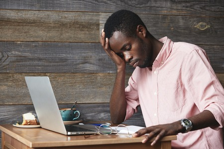 american banker: Overwork concept. Dark-skinned employee in pink shirt, sitting in front of laptop with tired and exhausted look, resting his elbow on table while working on new project, trying to focus on work
