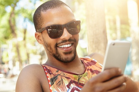 to tease: Attractive handsome African radio DJ with sly face expression typing message to his girlfriend with joke or tease using smart phone, smiling while enjoying sunny weather, sitting on bench in park Stock Photo