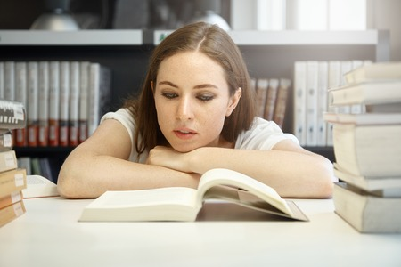 Cropped shot of tired freckled woman reading a book sitting at the table against library interior background, resting her head on hands, looking interested in plot. People and education concept
