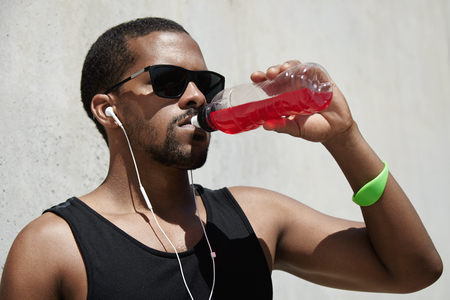 thirst quenching: Fitness and healthy lifestyle. Muscular build jogger in A-shirt holding plastic bottle of red juice, quenching his thirst, listening to music with earphones while resting after physical workout