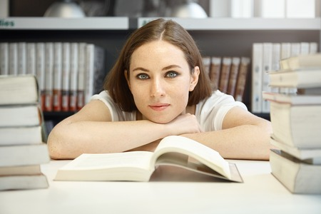 A-level student girl with freckles looking happy and calm, sitting in front of open textbook on Geography, studying foreign countries and nationalities. Young Caucasian woman reading at library Stock Photo