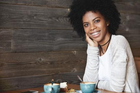 人間の感情や感情。魅力的でカリスマ的な浅黒い肌を持つ若い女性の巻き毛、中かっこで彼女の歯を見せて笑顔でポーズのケーキとコーヒーを飲み 写真素材