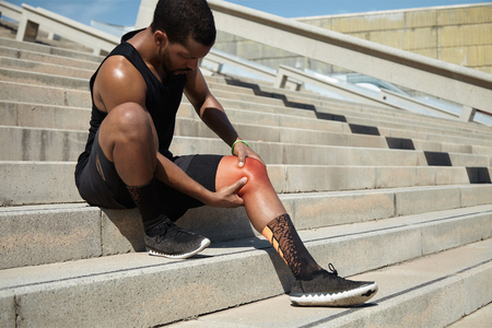 Physical injury concept. Attractive African runner with athletic body wearing black running shoes, sitting on steps on concrete stair, clutching injured knee in excruciating pain depicted in red color Stockfoto