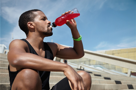 quenching: Handsome African runner with muscular arms and legs refreshing and quenching his thirst with juice or shake, drinking it from plastic bottle after running workout, sitting on steps of concrete stair