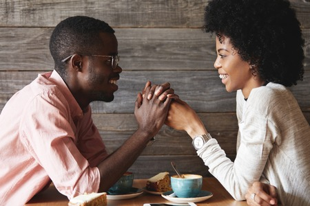 Dark-skinned young couple sitting at restaurant: black man in glasses holding his girlfriends hands, declaring his love to her or proposing on their anniversary day, both looking happy and cheerful