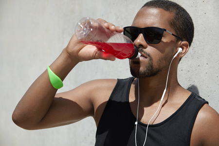 Attractive African sprinter with muscular arms, wearing stylish shades and tank top, refreshing and quenching his thirst with juice or shake, drinking it from plastic bottle after running workout