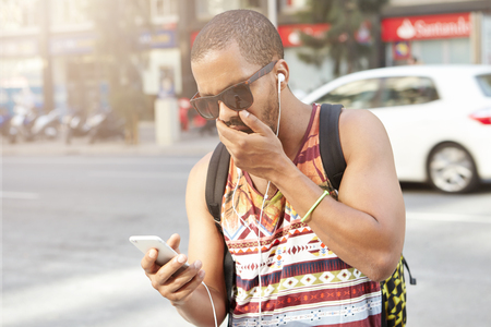 scandalous: Handsome African man wearing stylish sunglasses, looking at his mobile phone in shock, surpised with some unexpected or scandalous news, covering his mouth as browsing Internet on his way home Stock Photo