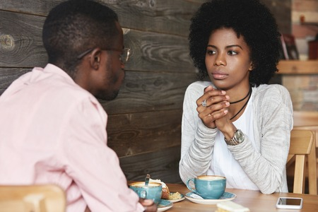 Close up portrait of African American friends at cafe having serious conversation, fashionable hipster woman with Afro hairstyle looking at her boyfriend with puzzled and thoughtful face expression