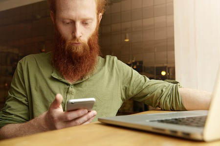distant work: Young freelancer with long red beard dressed casually holding smart phone, reading message via email or social networks while using laptop computer for distant work at coffee shop. Selective focus Stock Photo