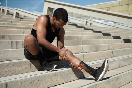 calf strain: Handsome black runner with muscular athletic body holding his leg with both hands, feeling pain in knee or calf, massaging it, suffering from strain or spasm while sitting on steps of concrete stair