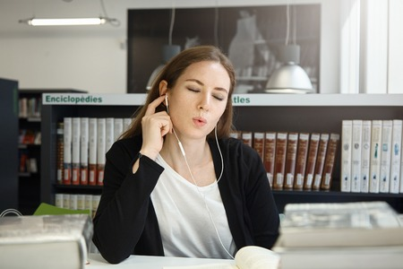 Young brunette woman listening to music with earphones, having fun instead of preparing for exams. Lazy student girl relaxing while studying at university library, closing her eyes and singing along Stock Photo